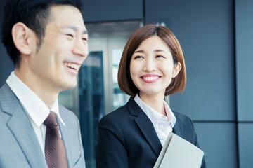 エレベーター前で話すスーツ姿の男女