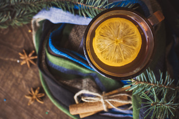 Cup of lemon tea covered with scarf. Christmas tree in background. Winter concept.