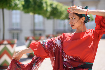 Young spanish woman in a red blouse and green pants. Fashion latin look. Flamenco woman smiling