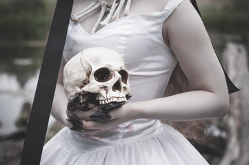 Human skull in creepy bride hands. Halloween concept