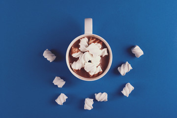 Hot chocolate with marshmallow candies on blue paper background. Top view. Copy space. Toned