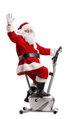 Santa Claus exercising on a stationary bicycle and waving