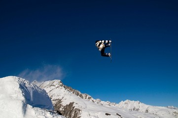 Snowboarder jumping, against blue sky, snow-covered mountain chain in the back, Andermatt, Switzerland, Europe