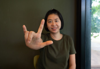 Asian woman using hand sign language I love you.