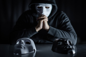 Hoodie man wearing mystery mask choosing black or white mask on the table. Anonymous social masking. Major depressive disorder or bipolar disorder. Halloween concept