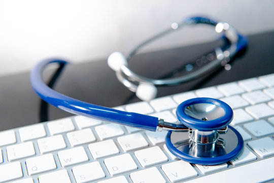 Medical science technology concept. Blue stethoscope on white modern keyboard on doctor desk. Health and wellness background. Global healthcare business. Computer antivirus protection