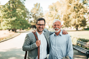 Portrait of two elegant smiling man in the park. Successful business family.