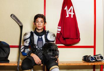 Boy sitting on the bench in ice hockey locker room