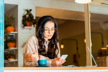 beautiful brunette woman using smartphone and laptop on coffee break at cafe