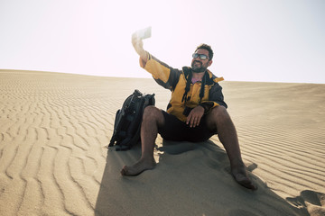 Hiker man with camera and backpack is resting sitting on the white sand in the desert by snapping up souvenir photo with smartphon and smiling. concept of technology and freedom