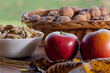 walnuts and red apples on a wooden table, autumn concept