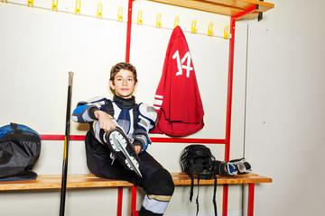 Hockey player putting on ice skates in locker room