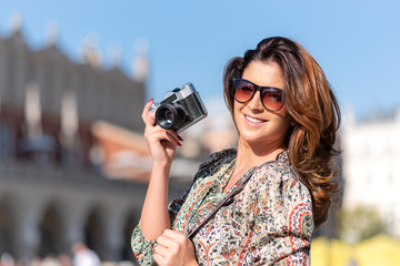 Beautiful and attractive woman holding a retro SLR camera and smiling on blurred background of a historic city