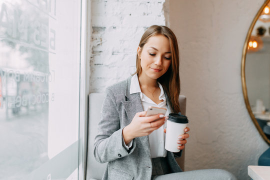 Young blogger girl with coffee sitting and working in a cafe. Bright portraits in the coffee shop, smiles and happy eyes. Business woman, strict style