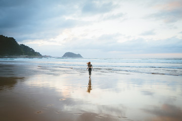 Anonymous female standing on wet beach