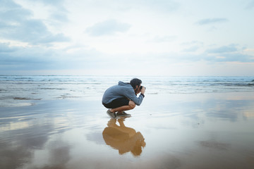 Young man taking pictures near sea