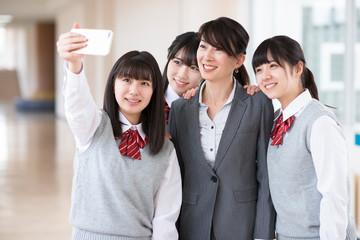 廊下で自撮りをする女子学生と女性教師