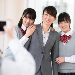 スマートフォンで写真を撮る女子学生と女性教師