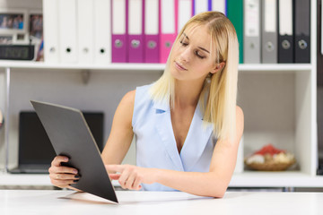 Studio photo of a beautiful blonde girl is talking in an office sitting at a table.