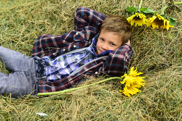 Theres nothing like the peace of the contryside. Little boy enjoy vacation in countryside. Little boy relax on hay. Live naturally