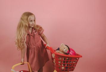 Retro inspired. Little shopaholic with shopping cart. Little girl shopping. Small girl in shop. Small shopper. I love shopping