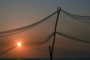 Decorative net in front of beach sunset