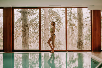 Young woman walking by the swimming pool
