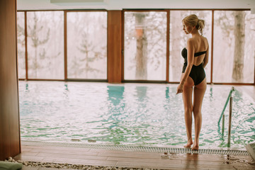 Young woman standing by the swimming pool