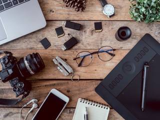 top view office table concept with coffee cup, digital camera, notebook, glasses, laptop and smartphone on wooden table background.
