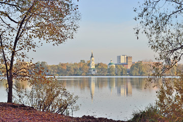the old church and other buildings stand on the opposite bank of the lake on an autumn day