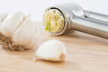 Close-up of a garlic clove and press