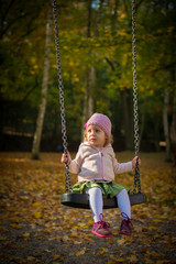 Little girl playing in Autumn park swing