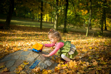 Little girl playing in Autumn park with truck toy