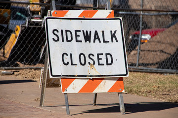 Sidewalk Closed standing sign on sidewalk in front of fence and construction equipment blurred in background