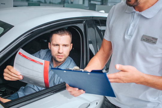 Seller stands at white car and holds tablet in hands. He point on it. Another man sits in car and holds insurance paper. He is serious and concentrated. They have conversation.