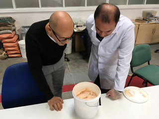 Lancaster University researchers Professor Mohamed Saafi and Hasan Hasan look into a bucket containing carrot mixture to be added to concrete, in their laboratory in Lancaster