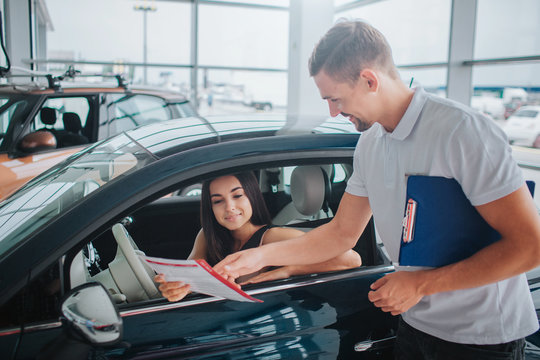 Nice consultant stands at black car and points on paper. He holds plastic tablet in other hand. Nice and young woman sits in car and looks at document. She is concentrated.