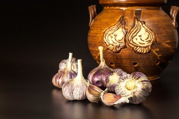 Open garlic on black background table. Whole and split fresh garlic on a black background. Traditional flu and cold treatment. Aromatic spices.