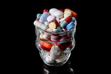 Pills and capsules of different colours and sizes in a Skull shot glass