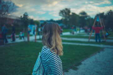 Young woman standing in playground at sunset