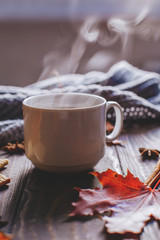 Wall Mural - Coffee mug with autumn maple leaves and women's woolen scarf on a wooden table