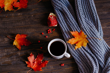 Fototapete - Coffee mug with autumn maple leaves and women's woolen scarf on a wooden table