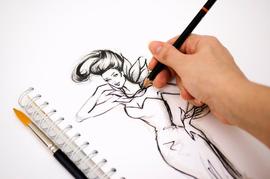 Close-up of an illustrator  hand drawing a fashion sketch