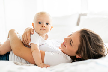 mother with baby on bed having good time