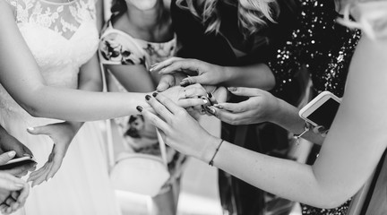 The bride shows her friends her wedding ring. Real emotions. Black and white photo.