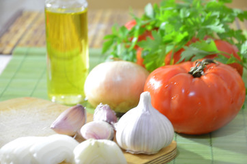 Chopped tomatoes on a board, onions, garlic, greens. Ingredients for cooking salad or soup. Healthy food diet. Photo on top of fresh vegetables, cutting board, oil, knife,