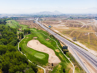 Golf Course in the middle of the city next to the highway