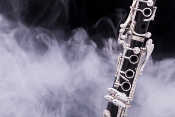 A black clarinet with silver plated keys in smoke on a black background