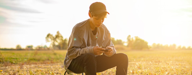 young person sitting in the middle of gorgeous amazing summer field and using smarphone f