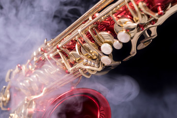 A red lacquered saxophone with gold plated keys in smoke on a black background